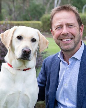 A bearded man wearing a blue checked shirt and jacket sitting in a garden alongside a yellow adult Labrador.